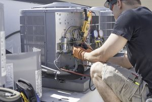 HVAC repair in Manasquan technician crouching in front of open condenser with a variety of tools