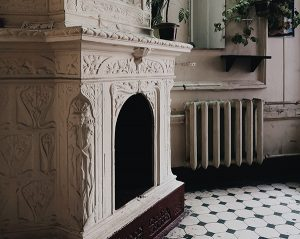 White radiator shown next to ornate white scrollwork fireplace on white and black tiled floor, Toms River boiler repair